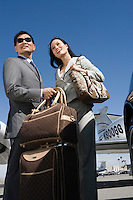Mid-adult businesswoman and businessman standing in front of car with their luggage.