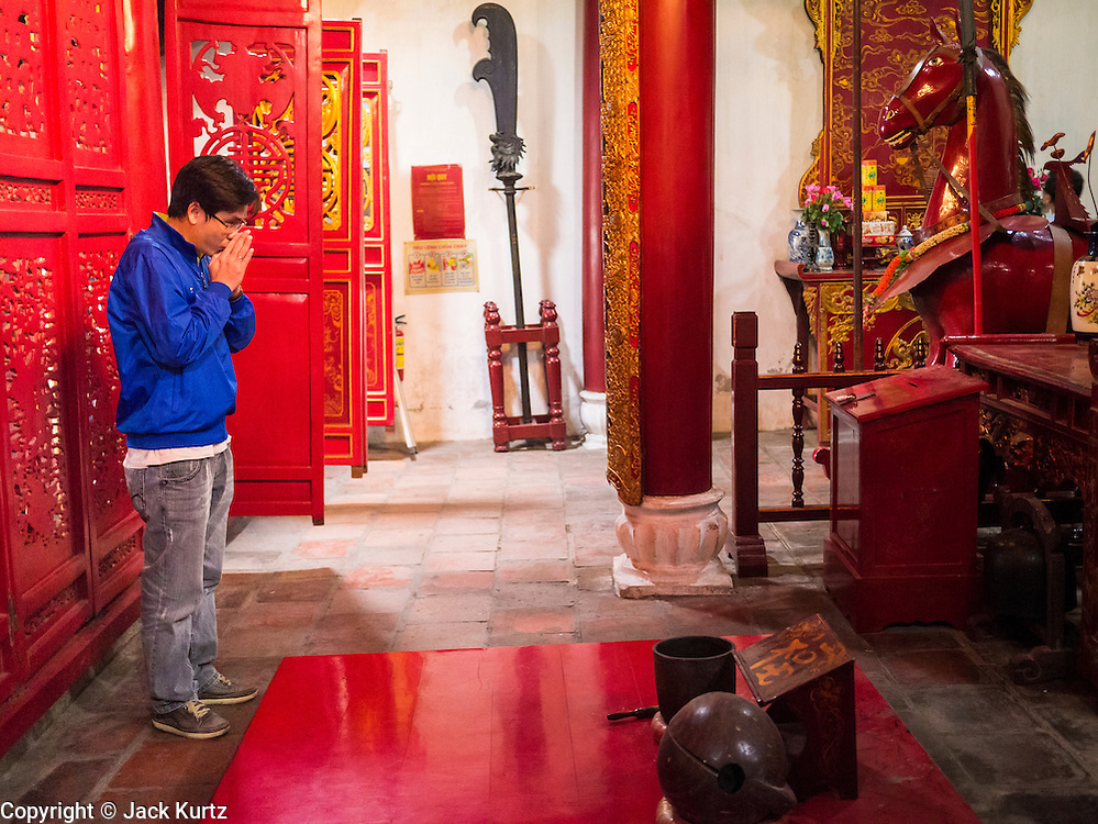 31 MARCH 2012 - HANOI, VIETNAM:   Vietnamese pray in Ngoc Son Temple, which was reportedly built during the Tran Dynasty (ca 1225) in the Old Quarter of Hanoi, Vietnam. The temple is dedicated to Tran Hung Dao, a Vietnamese national hero who defeated an invading Mongol army in the 13th century.     PHOTO BY JACK KURTZ