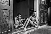Tan Tri, 21, and Tan Hau, 14 sit in the doorway of their Danang country side home. Both were born with physically disabilities to their legs, drastically limiting their movement and self-sufficiency. While mentally intact for the most part, They must be cared for around the clock by their mother, father and sisters.