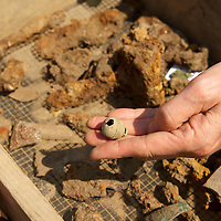 An archaeologist holds a metal bell in a dig tray at Historic Jamestowne.