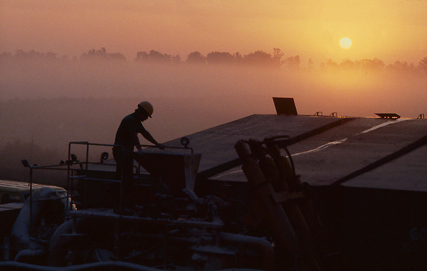 Stock photo of proppant tanks being inspected by oilfield worker at sunrise in East Texas