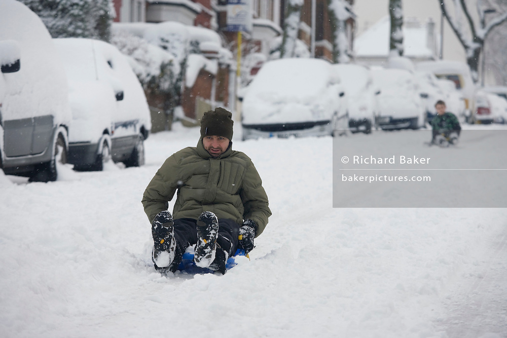 A local dad sledges down a hill in South London. Trying to pick up speed he holds his legs out in front to avoid too much breaking as deep snow has blocked this quiet road in Herne Hill, SE24. Behind the father is his son who also comes downhill, past parked cars that are all covered in snow - abandoned by owners who would otherwise have driven to work. settling on this part of London's inner-city - an unusual event - and the  heaviest precipitation for 18 years.