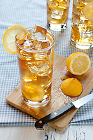 A glass of iced tea sits on a cutting board, garnished with a cut lemon. A half cut lemon with a paring knife sit on the cutting board.