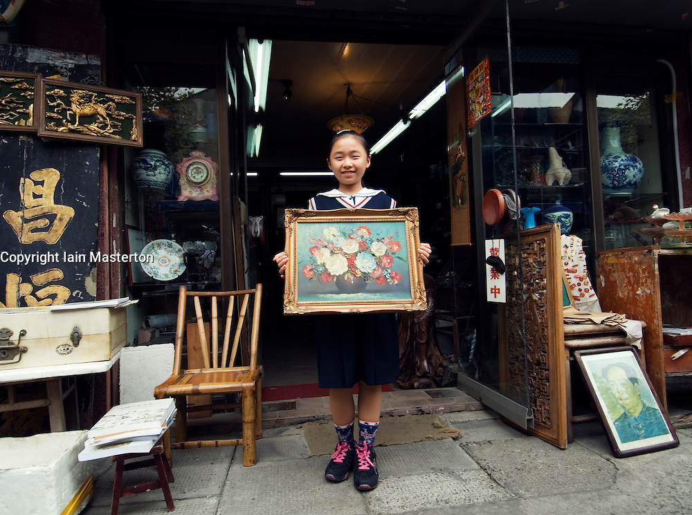 Girl displays painting outside art gallery in Dongtai Antiques Market in Shanghai