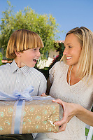 Boy giving birthday present to his mother