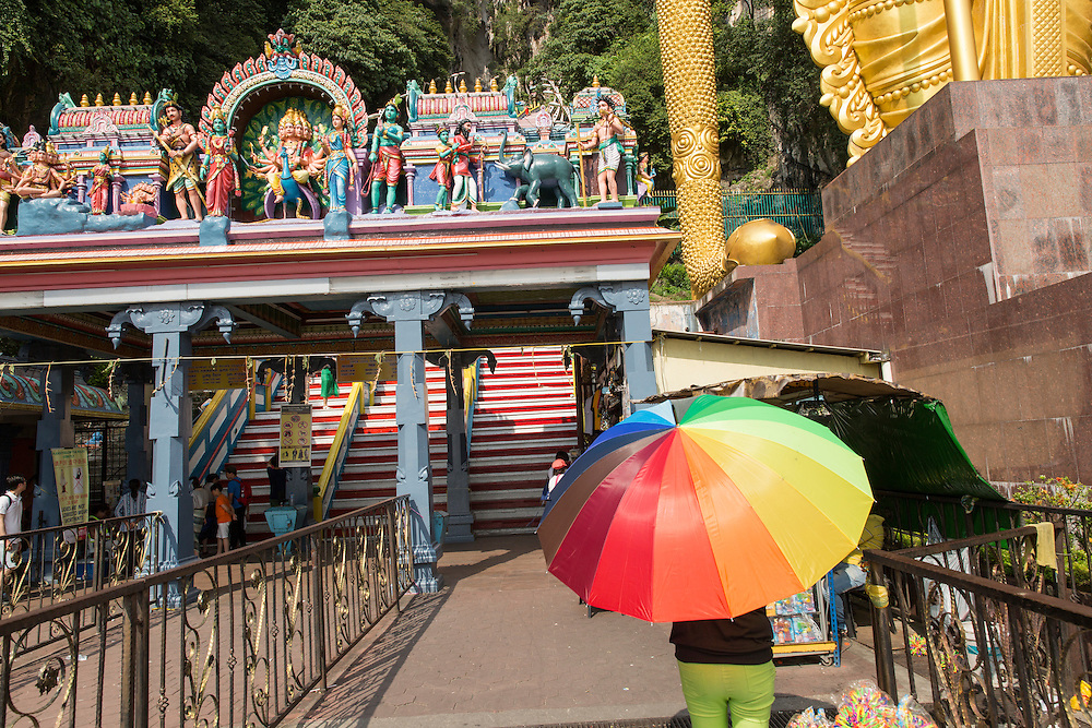 Asia, Malaysia, Kuala Lumpur, Visitor with colorful umbrella at entrance to Batu Caves, a Tamil Hindu shrine and tourist attraction