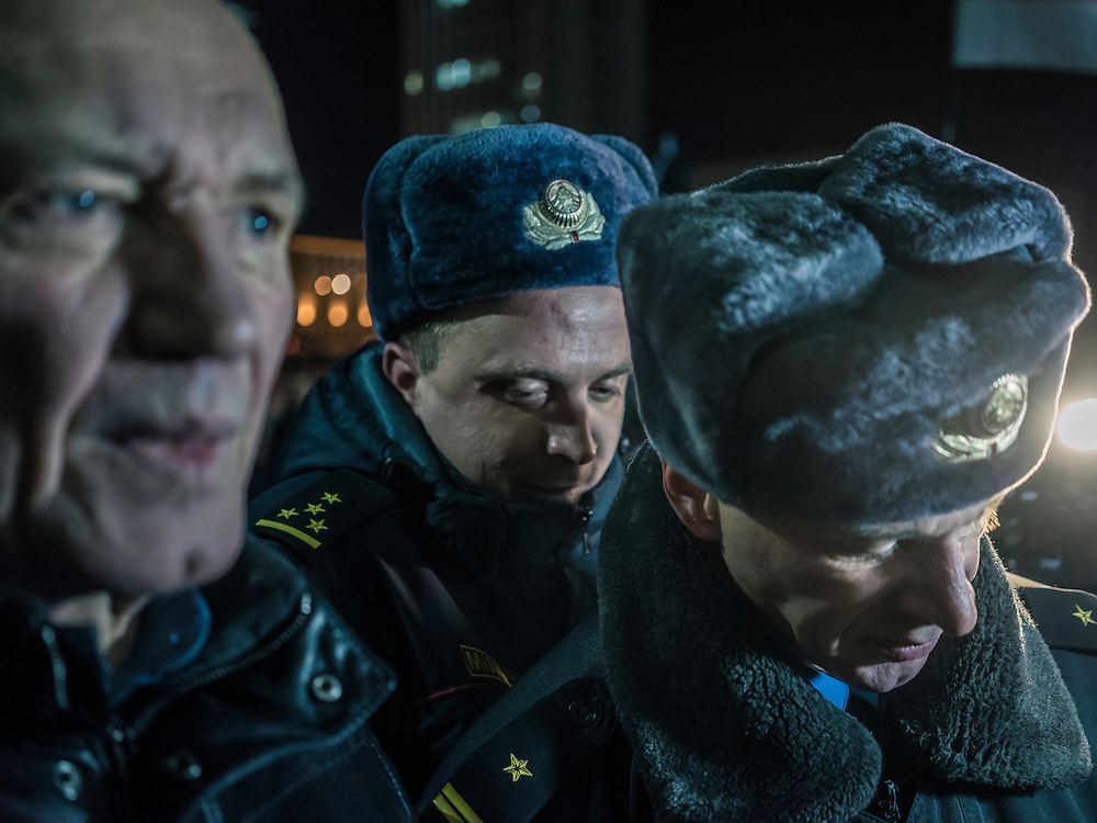 Police approach Mikalai Statkevich, a former opposition presidential candidate and political dissident, at a rally he organized to commemorate the nineteenth anniversary of a referendum which enshrined authoritarian changes in Belarus's constitution so they can fine him for holding an illegal rally on Tuesday, November 24, 2015 in Minsk, Belarus.