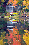 Canoes beached by the lake in Autumn in New Hampshire.
