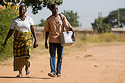 Vaccination team walking through village carrying an ice box with polio vaccines. Northern Ghana, Thursday November 13, 2008.