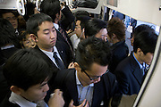 passengers pushing into an already full commuter train during rush hour Tokyo Japan