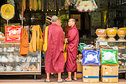 "12 NOVEMBER 2012 - BANGKOK, THAILAND:   Buddhist monks shop in a store that sells Buddhist supplies on Bamrung Muang Street in Bangkok. Thanon Bamrung Muang (Thanon is Thai for Road or Street) is Bangkok's ""Street of Many Buddhas."" Like many ancient cities, Bangkok was once a city of artisan's neighborhoods and Bamrung Muang Road, near Bangkok's present day city hall, was once the street where all the country's Buddha statues were made. Now they made in factories on the edge of Bangkok, but Bamrung Muang Road is still where the statues are sold. Once an elephant trail, it was one of the first streets paved in Bangkok. It is the largest center of Buddhist supplies in Thailand. Not just statues but also monk's robes, candles, alms bowls, and pre-configured alms baskets are for sale along both sides of the street.    PHOTO BY JACK KURTZ"
