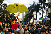 A gay man holds an umbrella and sign saying Just Love above the crowd at the 2014 gay pride march.