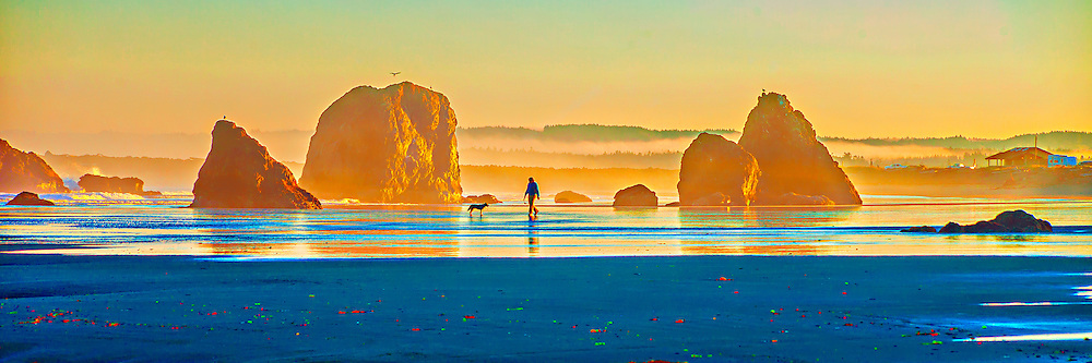 Photographic panorama of a man walking his dog amid monolithic rocks at dawn on Bandon Beach, Oregon