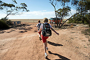 12 year old Pippa Reilly and 10 year old James Reilly run to catch the bus that will take them to school in Wyalkatchem,.Western Australian Wheatbelt. 11 December 2012 - Photograph by David Dare Parker