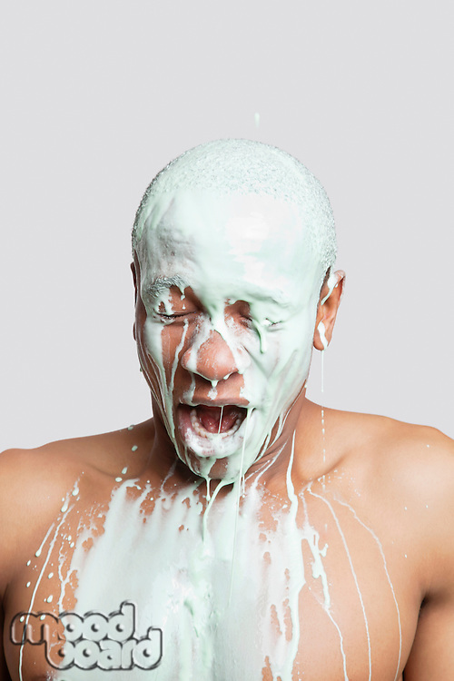 Shirtless young man covered in paint with mouth open against gray background