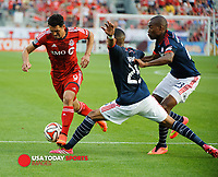 Aug 30, 2014; Toronto, Ontario, CAN; Toronto FC forward Gilberto Oliveira Souza Junior (9) moves past New England Revolution defenders Darrius Barnes (25) and Jose Goncalves (23) at BMO Field. New England won 3-0. Mandatory Credit: Peter Llewellyn-USA TODAY Sports