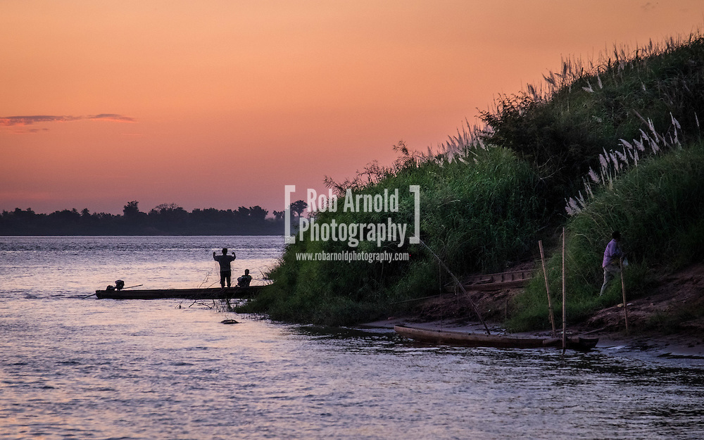 Fishermen working at dusk on the banks of the Mekong