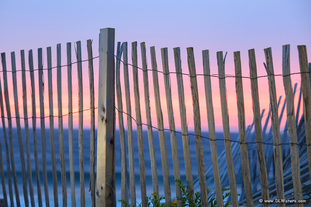 Pink and blue color in the sky just before the sun rises behind a  sand fence at Kitty Hawk pier.