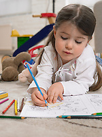 Girl (3-4) with colouring book on floor in home