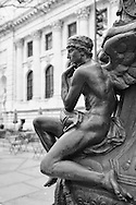 A pensive winged sculpture at  the base of one of the flagpoles on the east terrace of New York Public Library.<br /> The bronze flagpole bases were created by Raffaele Menconi and the Tiffany Studios and have been called the most beautiful in the country.