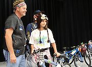 A Coop ES student receives their free bike from the Thin Blue Line Law Enforcement Motorcycle Club.