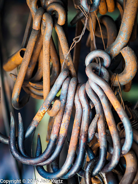 25 JANUARY 2016 - BANGKOK, THAILAND: Hooks and chain links hang in workshop that makes heavy chains for boat anchors. The metal for the chains is heated until it glows red and then it's pounded into shape. The Talat Noi neighborhood in Bangkok started as a blacksmith's quarter. As cars and buses replaced horse and buggy, the blacksmiths became mechanics and now the area is lined with car mechanics' and blacksmiths' shops.         PHOTO BY JACK KURTZ