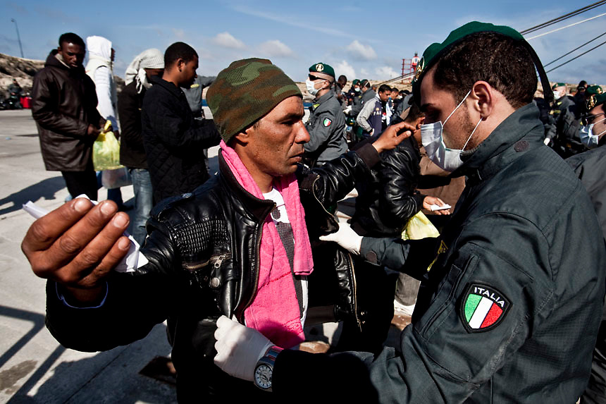 People fleeing unrest in Tunisia are checked by Italian Guardia di Finanza before boarding a cruise liner to a different part of Italy, on the southern island of Lampedusa . Italian Prime Minister Silvio Berlusconi promised to clear thousands of illegal Tunisian migrants from Lampedusa by the weekend after an outcry over a humanitarian crisis on the tiny southern island