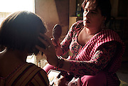 Sheza Shahnawaz, a 42 year old Hijra is the Guru (leader) assists Sonya, a 32 year old Hijra in make up for the evenings work on the streets of Karachi...The word Hijra is an Urdu word meaning eunuch or hermaphrodite. However, most Hijras in Pakistan are gay men who leave home to join the Hijra community as young boys where there is more acceptance. Most identify themselves as more feminine then masculine and dress and act accordingly...Although tolerated in a country where homosexuality is against the law, Hijras are largely ostracised from society. They are often denied work opportunities, rejected by most families, lack formal education and live in poorer areas of the city...They share similarities with the more famous Hijra communities in the Indian subcontinent and Bangladesh. In a continent where great emphasis is placed on one's ability to have children, those who are unfortunate not to be able to conceive children are not considered a true man or woman. Life for many Hijras in Pakistan consists of begging for alms (Zakat) in the more prosperous areas of the city as well as slums in addition to receiving alms when bestowing blessings on male babies and at weddings....Most Hijras dress as women, and engage in activities such as dancing and entertaining in public - activities that would be considered inappropriate for women of the subcontinent. Some members of the community engage in prostitution. .