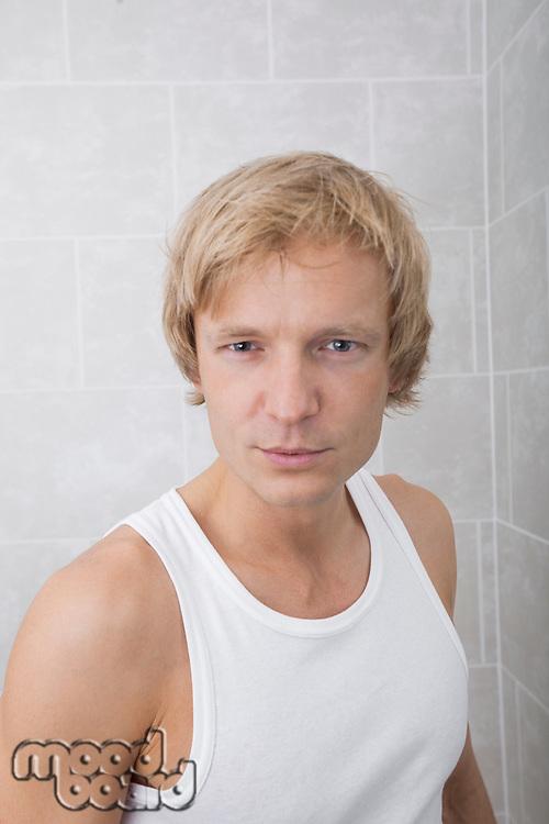 Portrait of handsome man standing in bathroom