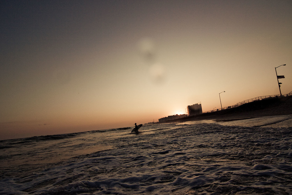 A surfer heads into the water at the 91st surf break at sunset, Rockaway Beach, NY, USA.