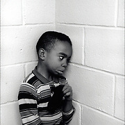 African American withdrawn lost in his own world, showing complete self-absorption. The child is severely developmental disabled and autistic in corner in private program in Bronx, NY.