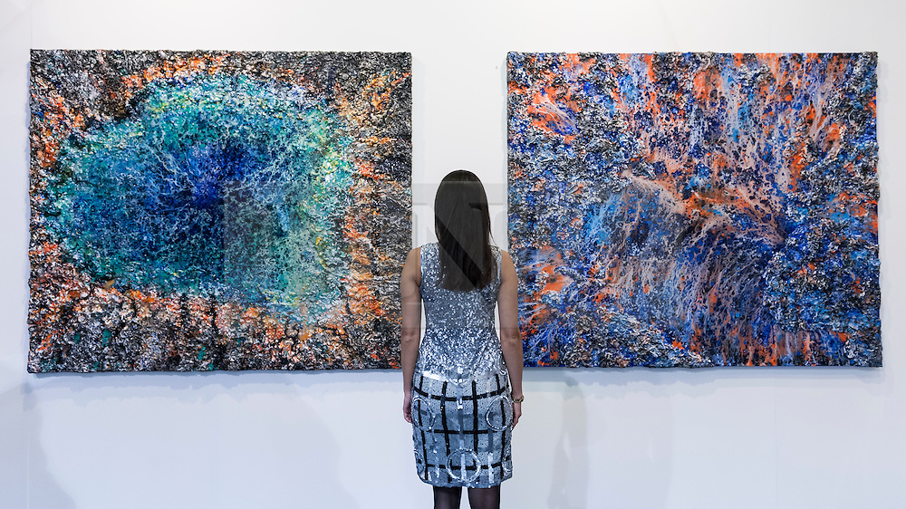 """© Licensed to London News Pictures. 19/05/2016. London, UK. Artist, Victoria Kovalenchikova, is seen with two of her works (L to R) """"The Earth"""" and """"The World"""".  Art16 opens at Olympia, in west London.  Now in its fourth edition, the fair brings together over 100 galleries from more than 30 countries showcasing a diverse cross-section of work by contemporary artists from around the world for buyers and art enthusiasts to visit. Photo credit : Stephen Chung/LNP"""