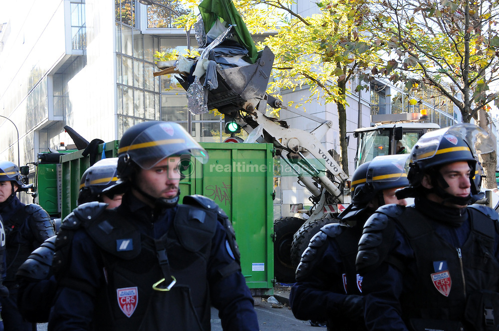"""French anti-riot policemen stand in front of migrants near the Jaures and Stalingrad metro stations, in northern Paris, France, on October 31, 2016, during a police operation aiming at a future evacuation of a migrant camp. An operation of """"administrative control"""" was underway on early October 31 in the Jaures/Stalingrad quarter before a future evacuation, whose date has not yet been set, according to a police source. The makeshift camp on the outskirts of the 10th and 19th arrondissements in the north of the capital numbers today 2,500 people, according to the City of Paris. Photo by Alain Apaydin/ABACAPRESS.COM"""