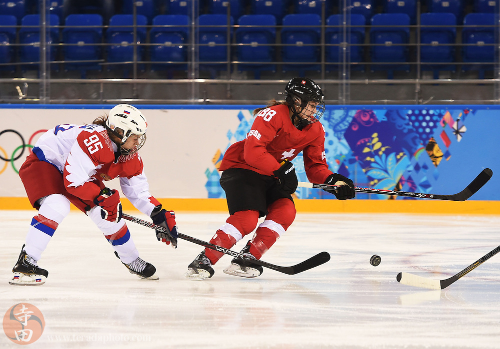 Feb 15, 2014; Sochi, RUSSIA; Switzerland forward Phoebe Stanz (88) and Russia forward Yelena Dergachyova (95) chase after the puck in a women's quarterfinals ice hockey game during the Sochi 2014 Olympic Winter Games at Shayba Arena.