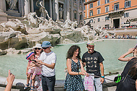 """ROME, ITALY - 20 JUNE 2017: A family and a couple takea a selfie in front of the Trevi Fountain in Rome, Italy, on June 20th 2017.<br /> <br /> The warm weather has brought a menacing whiff of tourists behaving badly in Rome. On April 12, a man went skinny-dipping in the Trevi fountain resulting in a viral web video and a 500 euro fine.<br /> <br /> Virginia Raggi, the mayor of Rome and a national figurehead of the anti-establishment Five Star Movement,  issued an ordinance involving harsher fines for eating, drinking or sitting on the fountains, for washing animals or clothes in the fountain water or for throwing anything other than coins into the water of the Trevi Fountain, Bernini's Four Fountains and 35 other city fountains of artistic or historic significance around the city.  """"It is unacceptable that someone use them to go swimming or clean themselves, it's an historic patrimony that we must safeguard,"""" Ms. Raggi said."""