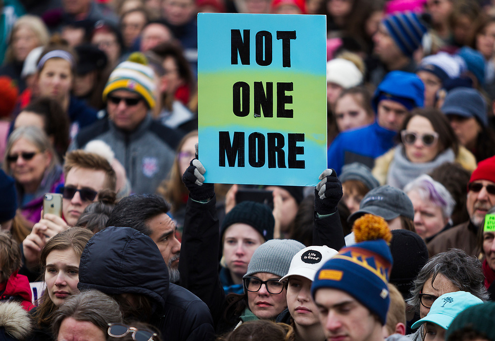 Demonstrators hold protest signs during the March for our Lives protest in Madison, Wisconsin, Saturday, March 24, 2018.