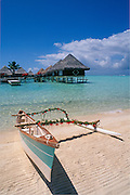 Outrigger canoe on beach and bungalows built over lagoon at Intercontinental Le Moana Bora Bora resort, Tahiti..