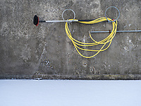Yellow hose with a brush to wash cars. Vestmannaeyjar islands, Iceland.