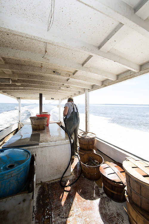 Ryan Ribb and Chris Shipley clean up the boat and secure the tops on the baskets filled with crab as they head home. | October 11, 2015