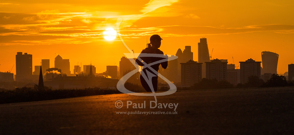 Primrose Hill, London, October 28th 2016. An early morning runner reaches the summit of Primrose Hill as the sun rises over London's skyline.