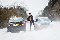 © Licensed to London News Pictures 02/03/2108, Cirencester, UK. A motorist stuck on the Gloucester road between Cirencester and Gloucestser  digging himslef out of the  snow drifts covering the road . Photo Credit : Stephen Shepherd/LNP