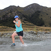 Runner Bex Topping crosses  Moke Creek on the Ben Lomond High Country Station during the Pure South Shotover Moonlight Mountain Marathon and trail runs. Moke Lake, Queenstown, New Zealand. 4th February 2012. Photo Tim Clayton