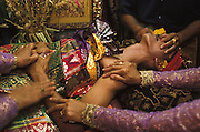 A Brahman filing the teeth of a young man at a traditional tooth-filing ceremony in Denpasar, Bali, Indonesia, while female relatives hold the boy's arms and shoulder. The ceremony is a puberty rite, done after the girl has had her first menstruation or the boy's voice has broken, but can be saved until later in life, sometimes until the time of ones wedding. The six front teeth in the upper jaw are filed down to an even row, the purpose of which is to lessen six human vices, e g anger and sexual desire. Another reason is to make one look less like a fanged demon, thereby securing ones entry into the land of the dead after cremation. The boy wears ceremonial brocade clothing.