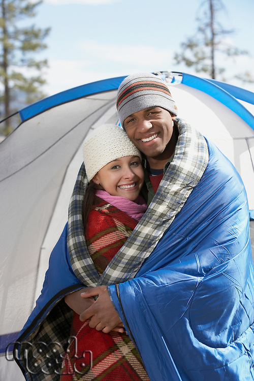 Young couple standing at campsite wrapped in blankets.