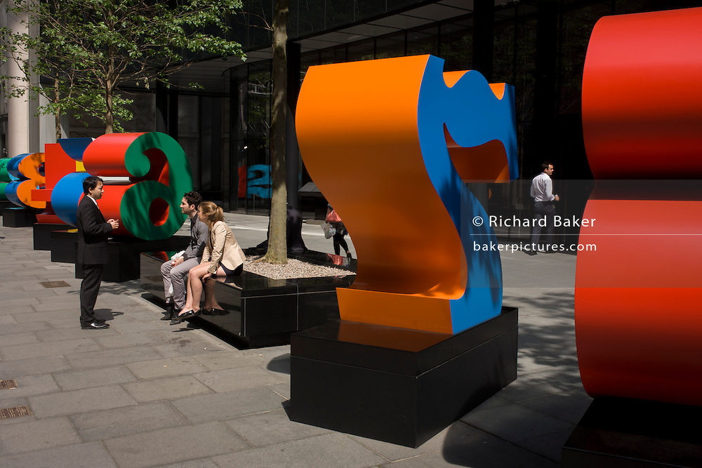 City workers talk by an art installation entitled 'One Through Zero (The Ten Numbers)' by American pop artist Robert Indiana (b 1928), in Lime Street, City of London, the capital's Square Mile, and its financial heart.