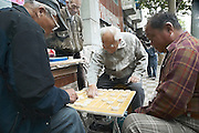 Old men playing checkers on the street in Shanghai, China,