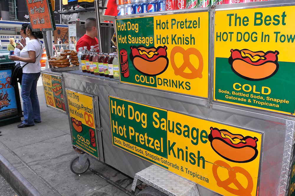 A street vendor selling hot dogs, pretzels, knishes, soft drinks, ice teas, and bottled water located on W. 42nd St. in Times Square.