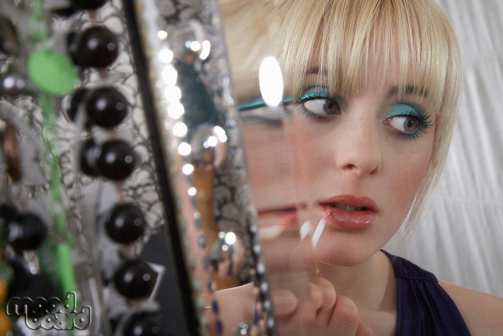 Teenage girl (16-17) applying lip gloss