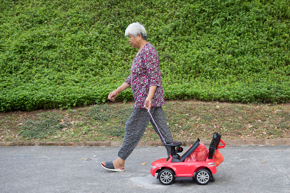 A women uses a child's pedal car to carry groceries beside Lower Delta Road, Singapore.