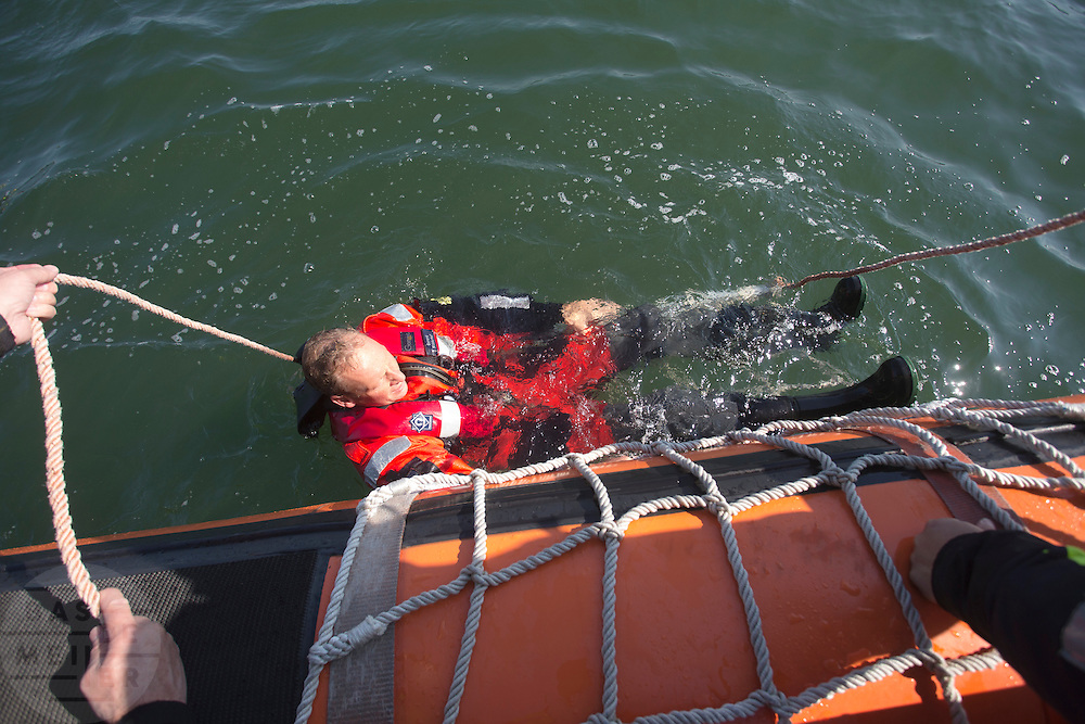 Een 'drenkeling' wordt aan boord gehaald van de KNRM reddingboot.<br />